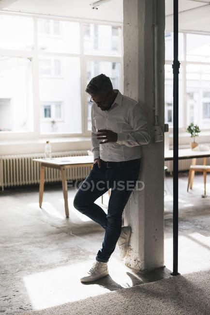 Hombre de negocios apoyado en pilar - foto de stock