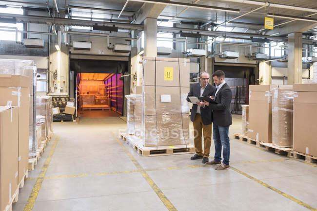 Deux hommes parlent dans l'entrepôt de l'usine — Photo de stock