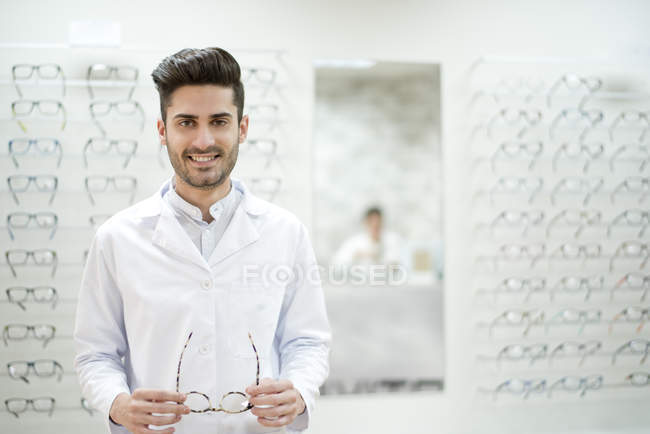 Optician holding glasses in shop — Stock Photo