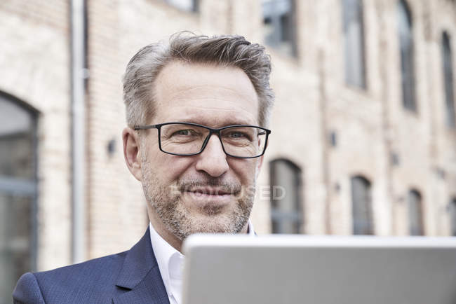 Businessman with tablet looking at camera — Stock Photo