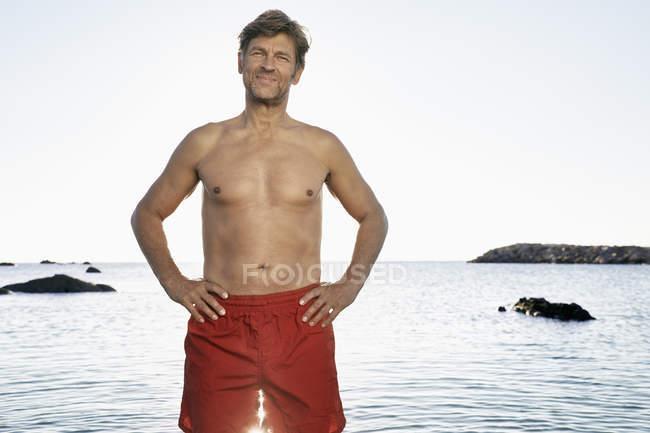 Mature man standing at waterside — Stock Photo