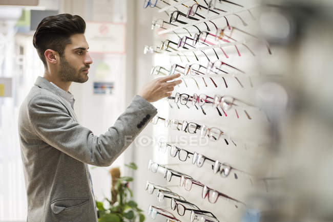 Man looking for glasses at optician shop — Stock Photo