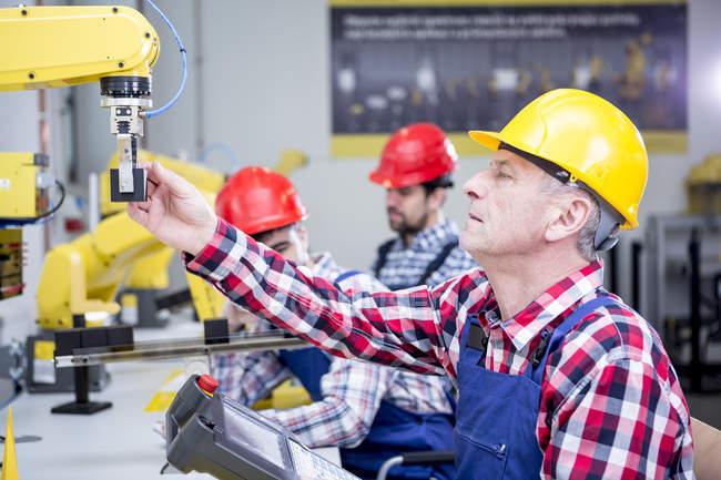 Man wearing hard hat adjusting industrial robot — Stock Photo
