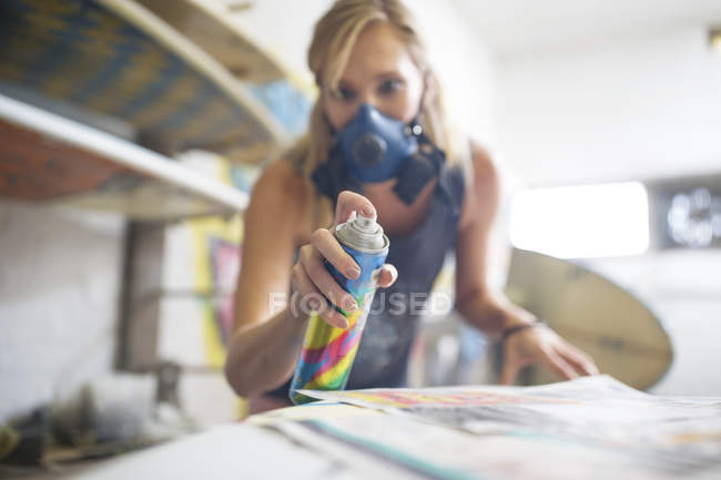 Surfshop employee spraying surfboard — Stock Photo