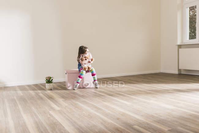 Fille assise sur la boîte et tenant ours en peluche dans un appartement vide — Photo de stock