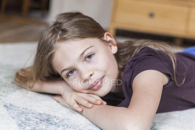 Menina deitada no tapete — Fotografia de Stock