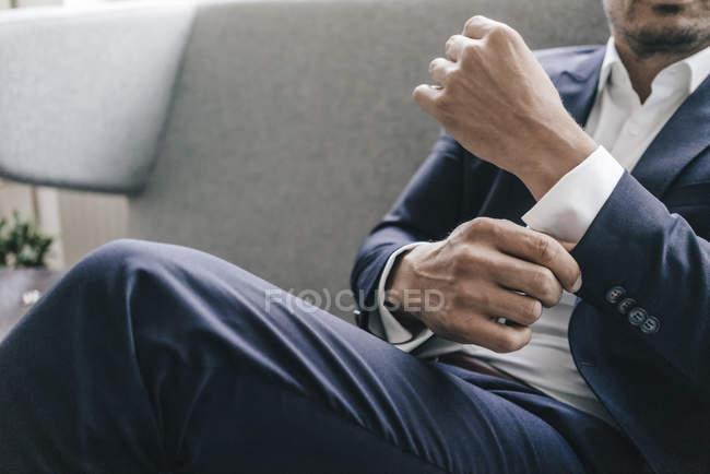 Businessman adjusting sleeves — Stock Photo