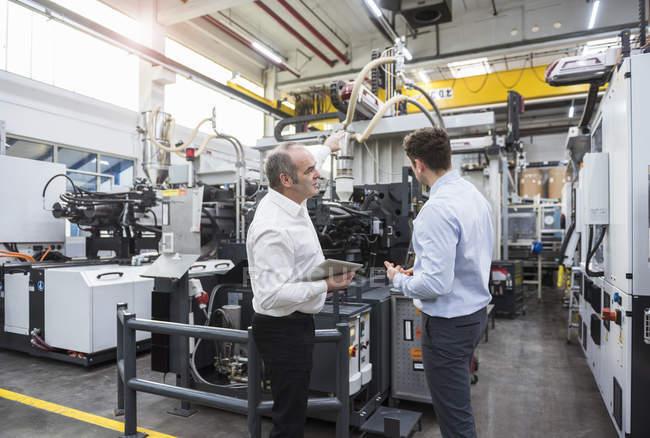 Homens com tablet discutindo na fábrica — Fotografia de Stock