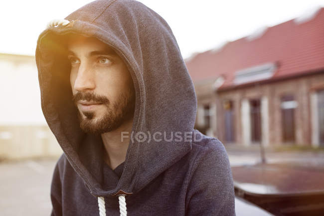 Portrait of bearded young man wearing hooded jacket — Stock Photo