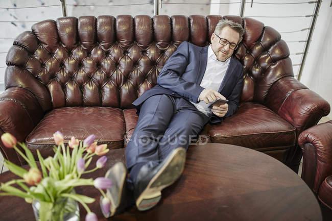 Homme d'affaires sur le canapé en utilisant un smartphone — Photo de stock