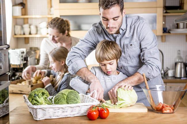 Family preparing salad in kitchen — Stock Photo