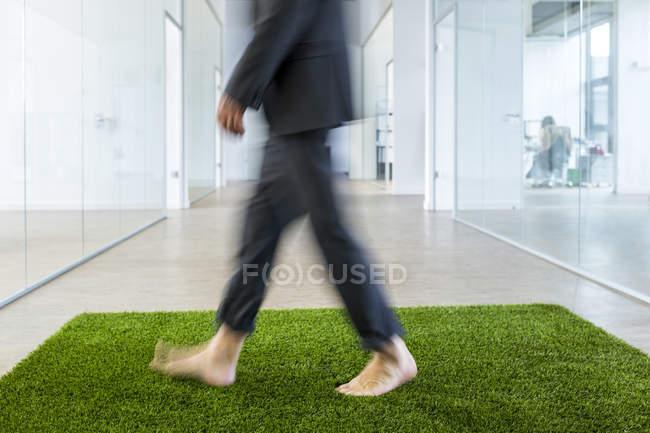 Homme d'affaires marchant sur le tapis d'herbe — Photo de stock