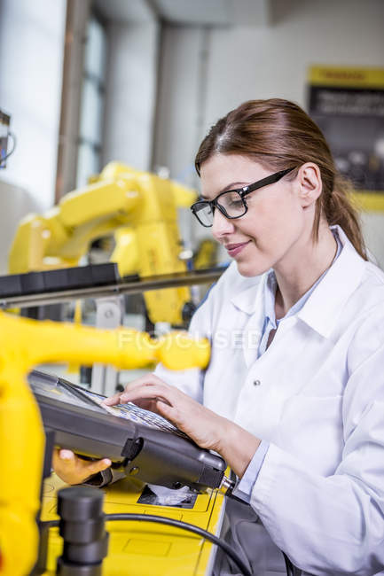 Woman using device in factory with industrial robots — Stock Photo