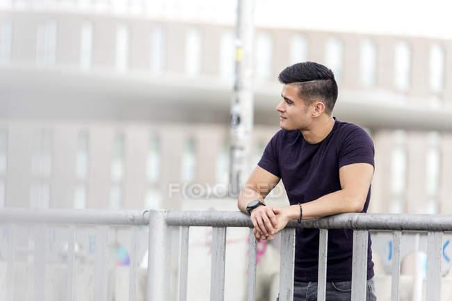 man leaning on railing stock photo 165701988