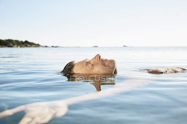 Man floating in the sea — Stock Photo