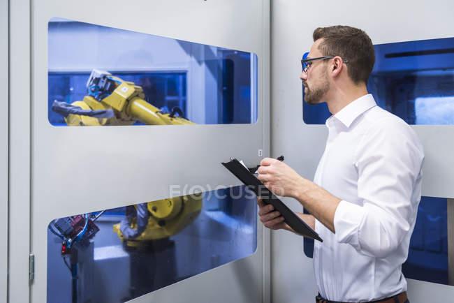 Hombre tomando notas en máquina robótica - foto de stock