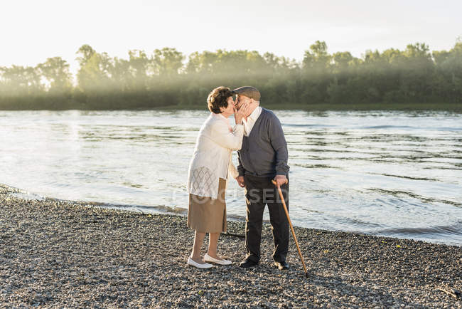Senior couple kissing on beach — Stock Photo