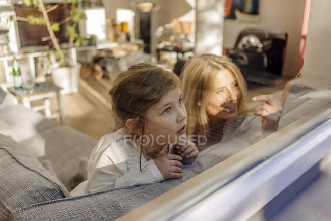 Woman and girl looking out of window — Stock Photo