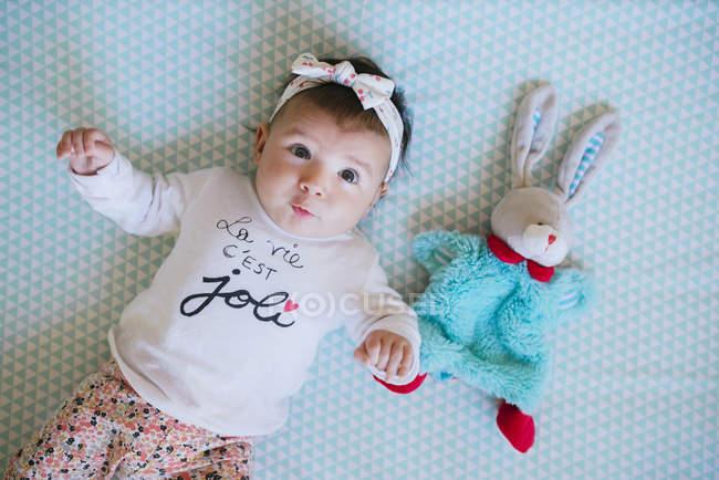 Bambina sdraiata con coniglietto giocattolo — Foto stock