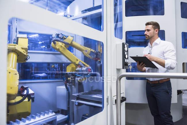 Homem tomando notas na máquina robótica — Fotografia de Stock