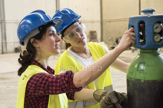 Female workers adjusting welding torch — Stock Photo