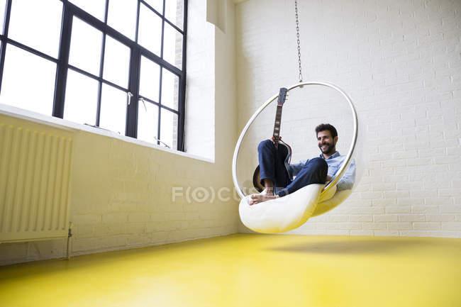 Homme à la guitare sur une chaise d'oscillation — Photo de stock