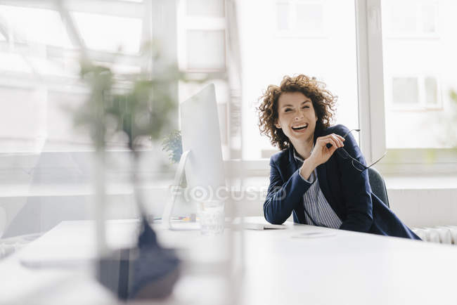 Laughing businesswoman at desk — Stock Photo