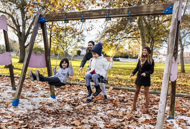 Amily having fun with swings — Stock Photo