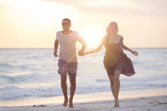 Couple running on beach — Stock Photo
