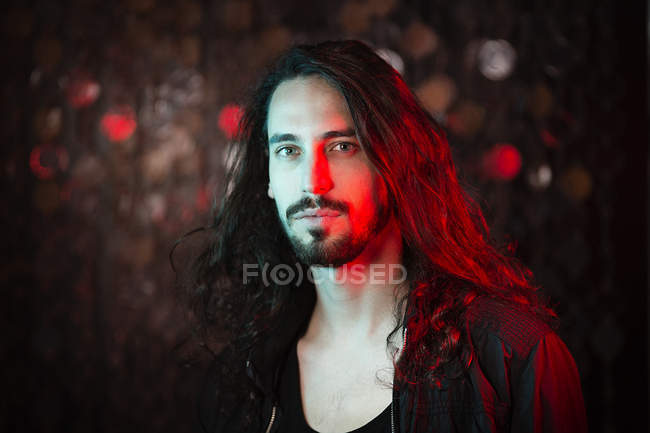 Portrait of bearded long-haired young man in red light — Stock Photo