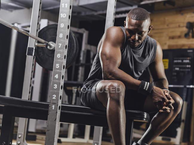 Атлет, сидящий в спортзале — стоковое фото