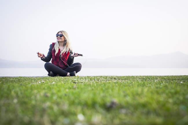 Sorrindo mulher loira sentada no prado — Fotografia de Stock