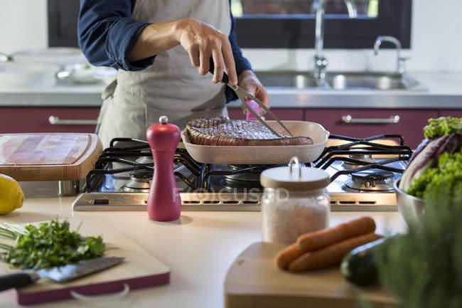 Jeune homme préparant teck grillé — Photo de stock