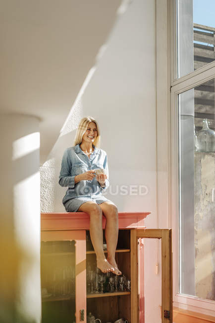Woman sitting on cupboard — Stock Photo