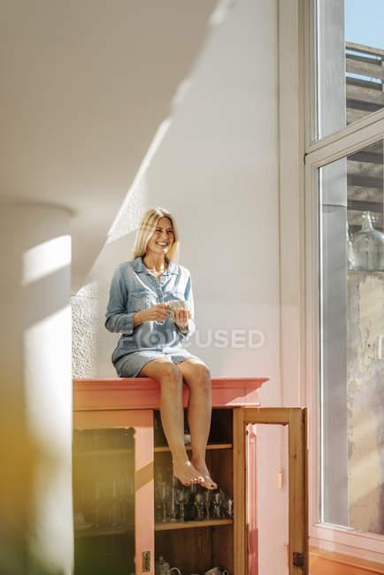 Femme assise sur le placard — Photo de stock