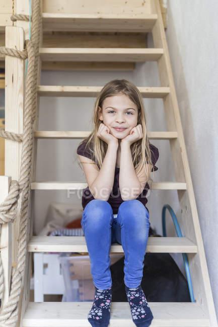Jeune fille assise sur l'échelle du lit surélevé — Photo de stock