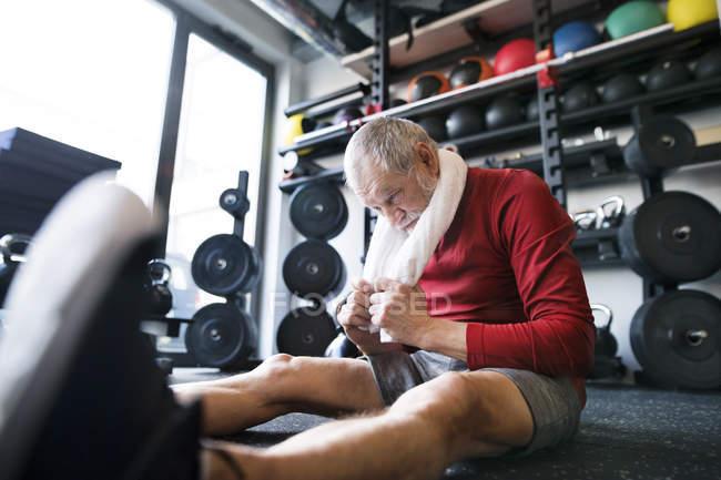 Exhausted senior man sitting on floor — Stock Photo