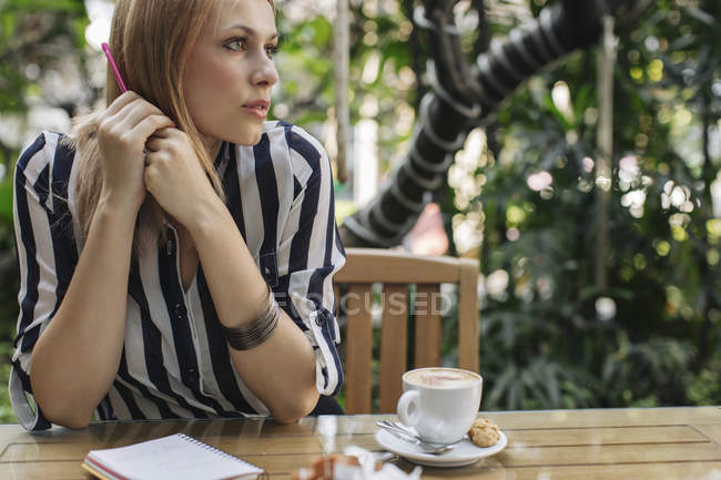 Pensive woman sitting at cafe — Stock Photo