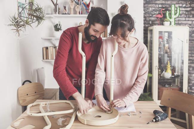 Couple assembling flat pack stool — Stock Photo