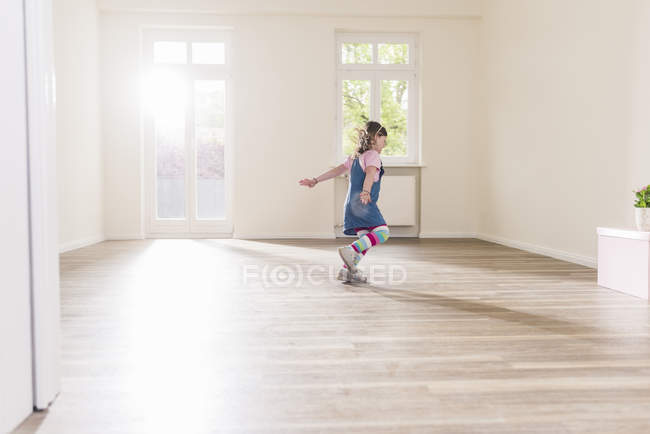 Happy girl running in empty apartment — Stock Photo