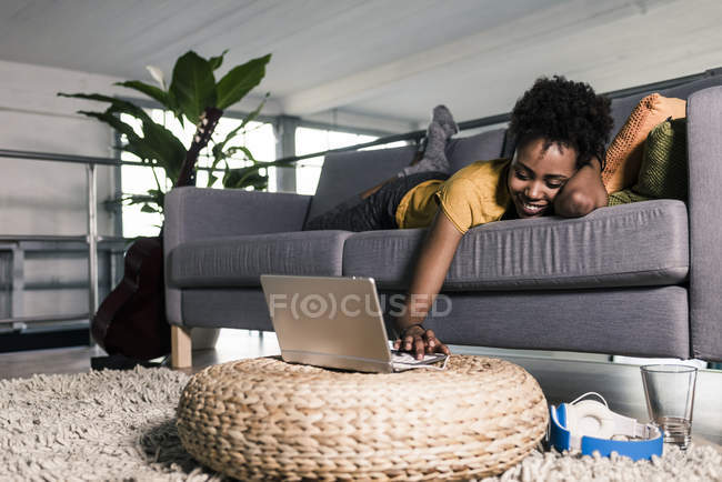 Femme sur canapé à l'aide d'ordinateur portable — Photo de stock
