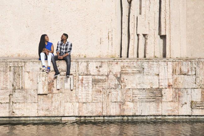 Paar sitzt auf Mauer am Wasser — Stockfoto