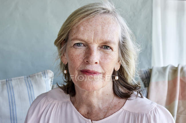 Senior woman sitting on couch — Stock Photo