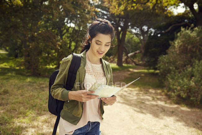 Woman in nature looking at map — Stock Photo