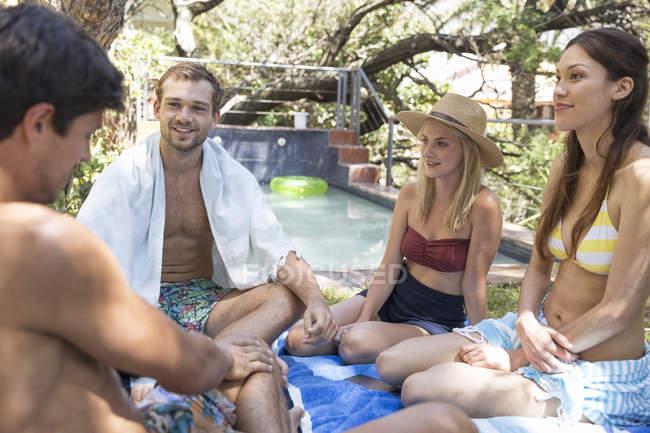 Amigos relajándose en el jardín junto a la piscina - foto de stock