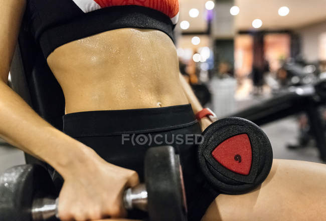 Woman lifting dumbbells in gym — Stock Photo