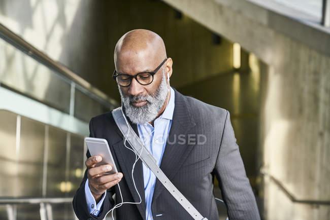 Uomo d'affari con smartphone in scala mobile — Foto stock
