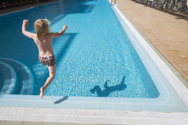 Boy jumping to swimming pool — Stock Photo
