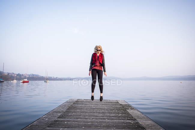 Femme blonde sautant dans l'air sur la jetée — Photo de stock