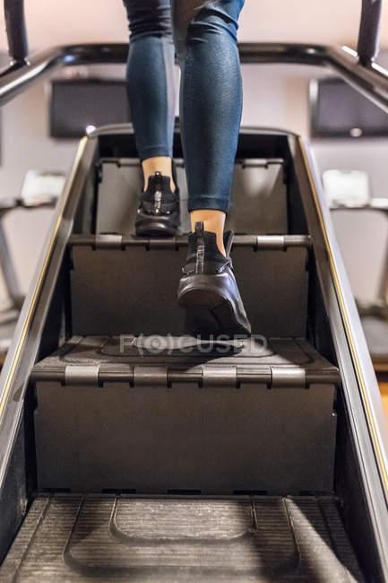 Femme de formation sur la machine d'escaliers dans la salle de gym — Photo de stock